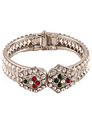 Classic, Elegant and timeless diamond bangle. This hexagonal patterned bangle is studded with white, red and green diamonds. This diamond base bangle is adjustable. Slight Color variations are possible due to differing screen and photograph resolution.