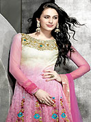 Ultimate collection of embroidered suits with fabulous style. This beautiful cream and onion pink kameez is nicely designed with embroidery work. Embroideri is done with resham, zari and sequins work in form of floral motifs. Embroidery on kameez is highlighting the beauty of this suit. The entire ensemble makes an excellent wear. Matching churidar and dupatta come along with this suit. This beautiful party wear suit is made with net fabric. Slight Color variations are possible due to differing screen and photograph resolutions.