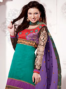 Look stunning rich with dark shades and floral patterns. The dazzling turquoise green and red chanderi silk churidar suit have amazing embroidery patch work is done with resham, zari, sequins and lace work. Beautiful embroidery work on kameez is stunning. The entire ensemble makes an excellent wear. Matching red churidar and contrasting purple dupatta is available with this suit. Slight Color variations are possible due to differing screen and photograph resolutions.