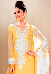 A desire that evokes a sense of belonging with a striking details. This yellow cotton jacquard churidar suit have amazing embroidery patch work is done with resham, stone and lace work. Embroidery on kameez is highlighting the beauty of this suit. Contrasting off white churidar and off white chiffon dupatta come along with this suit. Slight Color variations are possible due to differing screen and photograph resolutions.