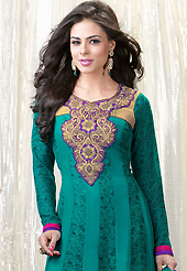 The glamorous silhouette to meet your most dire fashion needs. The dazzling turquoise green faux georgette churidar suit have amazing floral print and embroidery patch work is done with resham work. Beautiful embroidery work on kameez is stunning. The entire ensemble makes an excellent wear. Contrasting purple santoon churidar and turquoise green chiffon dupatta is available with this suit. Slight Color variations are possible due to differing screen and photograph resolutions.