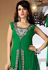 The glamorous silhouette to meet your most dire fashion needs. The dazzling green net readymade churidar suit have amazing embroidery and velvet patch work is done with zari, cutdana and stone work. The entire ensemble makes an excellent wear. Contrasting purple santoon churidar and green net dupatta is available with this suit. Slight Color variations are possible due to differing screen and photograph resolutions.
