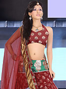 Get ready to sizzle all around you by sparkling lehenga. This maroon net and brocade lehenga is nicely embroidered patch work is done with resham, zari, sequins, stone and lace work. The beautiful embroidery on lehenga made it awesome and gives you stylish and attractive look to others. Matching choli and dupatta is availble with this lehenga. Slight Color variations are possible due to differing screen and photograph resolutions.