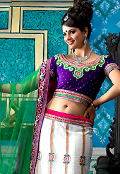 Take the fashion industry by storm in this beautiful embroidered lehengas. This white net a-line lehenga choli is nicely embroidered patch border is done with resham, zari, sequins, stone, beads and lace work. The beautiful embroidery on lehenga made it awesome and gives you stylish and attractive look to others. Contrasting dark purple velvet choli and green net dupatta is availble with this lehenga. Slight Color variations are possible due to differing screen and photograph resolutions.