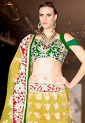 Embroidered lehengas are highly in order on a range of occasions such as wedding, formal party and festivals. This yellow net lehenga choli is nicely embroidered patch work is done with zari, gota patti and lace work. All over embroidery work on lehenga is stunning. The beautiful heavy embroidery on lehenga made it awesome and gives you stylish and attractive look to others. Contrasting green choli and yellow net dupatta is availble with this lehenga. Accessories shown in the image is just for photography purpose. Slight Color variations are possible due to differing screen and photograph resolutions.