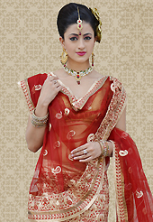 Embroidered lehengas are highly in order on a range of occasions such as wedding, formal party and festivals. This beige shimmer art silk a-line lehenga is nicely embroidered patch work is done with resham, zari and lace work. The beautiful embroidery on lehenga made it awesome and gives you stylish and attractive look to others. Matching choli and red net dupatta is availble with this lehenga. Slight Color variations are possible due to differing screen and photograph resolutions.