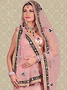 Bold colors created by the inventive drapes of textile catch the imagination like no other contemporary clothing. This dusty pink net a-line lehenga is nicely embroidered and velvet patch work is done with resham, stone and zardosi work. The beautiful embroidery on lehenga made it awesome and gives you stylish and attractive look to others. Matching choli and dupatta is availble with this lehenga. Slight Color variations are possible due to differing screen and photograph resolutions.