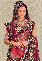 Make your collection more attractive and charming with this impressive dress. This pink net a-line lehenga is nicely embroidered and velvet patch work is done with stone, beads and cutbeads work. The beautiful embroidery on lehenga made it awesome and gives you stylish and attractive look to others. Matching choli and burgundy net dupatta is availble with this lehenga. Slight Color variations are possible due to differing screen and photograph resolutions.