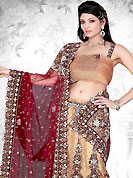 Embroidered lehengas are highly in order on a range of occasions such as wedding, formal party and festivals. This beige and maroon net lehenga choli is nicely embroidered patch work done with resham, zari, sequins, stone, cutdana, zardosi, swarovski and kasab worked rich embroidery on all over lehenga. The beautiful embroidery on lehenga made it awesome and gives you stylish and attractive look to others. Border on dupatta made it stylish and fabulous, gives you a stunning look. Matching choli and contrast maroon net dupatta is availble with this lehenga. The choli bust size can be customize upto 38 inches. Slight Color variations are possible due to differing screen and photograph resolutions.