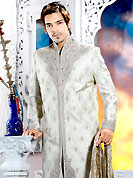 Make your collection more attractive with this dazzling sherwani. This off white sherwani embellished with sequins, beads, cutdana, heavy stone, zarkan, cutdana and patch work. The beautiful heavy embroidery on front border, collar, back and cuffs made it awesome and gives you stylish and attractive look to others. Matching churidar is enhanced your personality. This sherwani made with cotton silk fabric. Accessories shown in the image is just for photography purpose. Slight Color variations are possible due to differing screen and photograph resolutions.