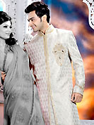 Emblem of fashion and style, each piece of our range of designer sherwani is certain to enhance your look as per todays trends. This off white sherwani embellished with zari, sequins, beads, stone and patch work. The beautiful heavy embroidery on front border, collar, back and cuffs made it awesome and gives you stylish and attractive look to others. Matching churidar is enhanced your personality. This sherwani made with jacquard fabric. Accessories shown in the image is just for photography purpose. Slight Color variations are possible due to differing screen and photograph resolutions.