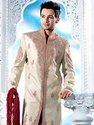 Emblem of fashion and style, each piece of our range of designer sherwani is certain to enhance your look as per todays trends. This cream sherwani embellished with zari, sequins, beads, stone and patch work. The beautiful heavy embroidery on front border, collar, back and cuffs made it awesome and gives you stylish and attractive look to others. Contrasting churidar is enhanced your personality. This sherwani made with jacquard fabric. Accessories shown in the image is just for photography purpose. Slight Color variations are possible due to differing screen and photograph resolutions.