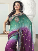 Your search for elegant look ends here with this lovely saree. This green and purple saree is beautifully designed with extensive embroidered border and butti patch work. Embroidery is done with resham, zari and sequins work. This fabulous party wear saree is specially crafted for your stunning and gorgeous look. This beautiful drape is crafted with crepe fabric. Matching blouse come along with this saree. Slight color variations are possible due to differing screen and photograph resolution.
