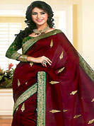 Let your personality articulate for you with this amazing embroidered saree. This deep maroon saree is nicely designed with embroidered and patch work. Embroidery is done with self weaving, resham and zari work in form of floral motifs. Beautiful embroidery patch border on saree make attractive to impress all. This saree gives you a modern and different look in fabulous style. This beautiful drape is crafted with art silk fabric. Matching blouse is available with this saree. Slight color variations are possible due to differing screen and photograph resolution.