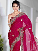 Dreamy variation on shape and forms compliment your style with tradition. This dark pink saree is nicely designed with embroidered and velvet patch work in fabulous style. Embroidery is done with zari, sequins, stone, kundan and cutdana work in form of floral motifs. Beautiful embroidery work on saree make attractive to impress all. This saree gives you a modern and different look in fabulous style. This beautiful drape is crafted with jacquard fabric. Matching blouse is available with this saree. Slight color variations are possible due to differing screen and photograph resolution.