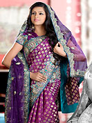 Get ready to sizzle all around you by sparkling saree. This purple half half brocade and net saree is nicely designed with embroidered and silk patch work in fabulous style. Embroidery is done with resham, zari, sequins, stone, cutdana and kasab work in form of floral motifs. Beautiful broad heavy embroidery patch border on saree make attractive to impress all. This saree gives you a modern and different look in fabulous style. Matching blouse is available with this saree. Slight color variations are possible due to differing screen and photograph resolution.