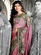 It is color this season and bright shaded suits are really something that is totally in vogue. This shaded pink shimmer faux georgete saree is nicely designed with embroidered and net patch work in fabulous style. Embroidery is done with resham, zari, sequins, stone, kasab and cutdana work in form of floral motifs. Beautiful embroidery work on saree make attractive to impress all. This saree gives you a modern and different look in fabulous style. Matching blouse is available with this saree. Slight color variations are possible due to differing screen and photograph resolution.