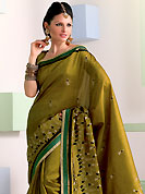 Make a trendy look with this classic embroidered saree. This olive green raw silk saree have beautiful embroidery patch work which is embellished with resham work. Fabulous designed embroidery gives you an ethnic look and increasing your beauty. Matching blouse is available. Slight Color variations are possible due to differing screen and photograph resolutions.