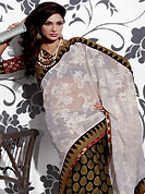 Dreamy variation on shape and forms compliment your style with tradition. This off white and black faux chiffon and viscose saree is nicely designed with embroidered floral design patch border is done with resham, zari and stone work. Saree gives you a singular and dissimilar look. Contrasting maroon blouse is available. Slight color variations are possible due to differing screen and photograph resolution.