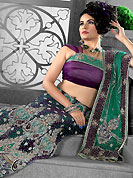 Elegance and innovation of designs crafted for you. This purple and green net lehenga style saree have beautiful embroidery and velvet patch work which is embellished with zari, sequins, stone, cutdana, kasab and cut motti work. Fabulous designed embroidery gives you an ethnic look and increasing your beauty. Matching blouse is available. Slight Color variations are possible due to differing screen and photograph resolutions.