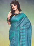 Dreamy variation on shape and forms compliment your style with tradition. This turquoise blue raw silk saree is nicely designed with floral, paisley and geometric print work. Saree gives you a singular and dissimilar look. Matching blouse is available. Slight color variations are possible due to differing screen and photograph resolution.