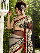 Take a look on the changing fashion of the season. This black and off white net lehenga style saree is nicely designed with embroidered patch work is done with resham, zari and stone work. Beautiful embroidery patch border on saree make attractive to impress all. This saree gives you a modern and different look in fabulous style. Matching black blouse is available with this saree. Slight color variations are possible due to differing screen and photograph resolution.