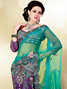 Try out this year top trend, glowing, bold and natural collection. This turquoise and purple net lehenga style saree is nicely designed with embroidered patch work is done with zari, stone, cutbeads and lace work. Saree gives you a singular and dissimilar look. Matching purple blouse is available. Slight color variations are possible due to differing screen and photograph resolution.