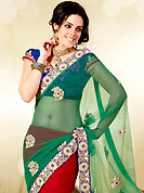 Make a trendy look with this classic embroidered saree. This green and red net lehenga style saree is nicely designed with embroidered patch work is done with zari, stone, beads and bullion work. Saree gives you a singular and dissimilar look. Contrasting blue blouse is available. Slight color variations are possible due to differing screen and photograph resolution.
