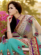 Exquisite combination of color, fabric can be seen here. This off white and aqua blue net saree is nicely designed with heavy embroidered patch work is done with resham, zari, beads, stone and kasab work. Beautiful embroidery patch border on saree make attractive to impress all. This saree gives you a modern and different look in fabulous style. Contrasting purple blouse is available with this saree. Slight color variations are possible due to differing screen and photograph resolution.
