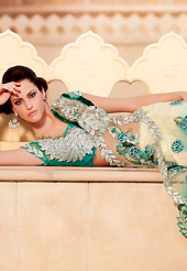 An occasion wear perfect is ready to rock you. This light cream and turquoise green net lehenga style saree is nicely designed with heavy embroidered patch work is done with resham, zari, sequins, stone and lace work. Beautiful embroidery patch border on saree make attractive to impress all. This saree gives you a modern and different look in fabulous style. Matching blouse is available with this saree. Slight color variations are possible due to differing screen and photograph resolution.