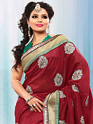 Take the fashion industry by storm in this beautiful embroidered saree. This dark red bhagalpuri silk saree is nicely designed with embroidered patch work is done with resham, zari and stone work. Saree gives you a singular and dissimilar look. Contrasting green blouse is available. Slight color variations are possible due to differing screen and photograph resolution.
