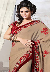 Exquisite combination of color, fabric can be seen here. This light brown faux chiffon saree is nicely designed with embroidered patch work is done with resham and stone work. Saree gives you a singular and dissimilar look. Contrasting maroon blouse is available. Slight color variations are possible due to differing screen and photograph resolution.