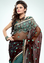 Get ready to sizzle all around you by sparkling saree. This deep brown and teal green net and georgette saree is nicely designed with embroidered patch work is done with resham, zari and sequins work. Saree gives you a singular and dissimilar look. Matching blouse is available. Slight color variations are possible due to differing screen and photograph resolution.