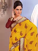 Dreamy variation on shape and forms compliment your style with tradition. This beautiful yellow chiffon saree is nicely designed with floral, paisley print, zari and graceful patch border. Beautiful print work on saree make attractive to impress all. It will enhance your personality and gives you a singular look. Contrasting maroon blouse is available with this saree. Slight color variations are due to differing screen and photography resolution.
