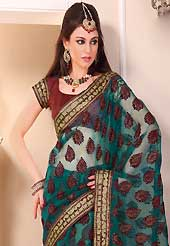 Exquisite combination of color, fabric can be seen here. This beautiful teal green tissue saree is nicely designed with velvet, gold print, zari, lace and graceful patch border. Beautiful print work on saree make attractive to impress all. It will enhance your personality and gives you a singular look. Contrasting maroon blouse is available with this saree. Slight color variations are due to differing screen and photography resolution.