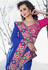 Exquisite combination of color, fabric can be seen here. This shaded blue faux georgette jacquard and net lehenga style saree have beautiful embroidery patch work which is embellished with resham, zari and stone work. Fabulous designed embroidery gives you an ethnic look and increasing your beauty. Contrasting dark pink art silk blouse is available. Slight Color variations are possible due to differing screen and photograph resolutions.