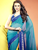 A desire that evokes a sense of belonging with a striking details. This beautiful teal blue and blue faux georgette saree is nicely designed with abstract, gold print and graceful patch border. Beautiful print work on saree make attractive to impress all. It will enhance your personality and gives you a singular look. Matching blouse is available with this saree. Slight color variations are due to differing screen and photography resolution.