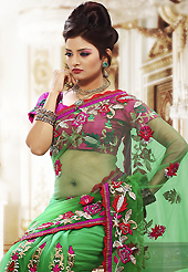 Envelope yourself in classic look with this charming saree. This green net saree is nicely designed with embroidered patch work is done with resham, zari and stone work. Beautiful embroidery work on saree make attractive to impress all. This saree gives you a modern and different look in fabulous style. Contrasting dark pink blouse is available. Slight color variations are possible due to differing screen and photograph resolution.