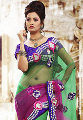 The evolution of style species collection spells pure femininity. This shaded green and pink net saree is nicely designed with embroidered patch work is done with resham, zari and stone work. Beautiful embroidery work on saree make attractive to impress all. This saree gives you a modern and different look in fabulous style. Contrasting purple blouse is available. Slight color variations are possible due to differing screen and photograph resolution.