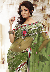 It is color this season and bright shaded suits are really something that is totally in vogue. This green net and brasso saree is nicely designed with embroidered patch work is done with resham, zari and sequins work. Beautiful embroidery work on saree make attractive to impress all. This saree gives you a modern and different look in fabulous style. Matching blouse is available. Slight color variations are possible due to differing screen and photograph resolution.