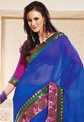 Elegance and innovation of designs crafted for you. This blue net saree is nicely designed with embroidered patch work is done with zari work. This saree gives you a modern and different look in fabulous style. Contrasting magenta blouse is available. Slight color variations are possible due to differing screen and photograph resolution.