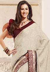 It is color this season and bright shaded suits are really something that is totally in vogue. This off white jacquard saree is nicely designed with embroidered patch work is done with resham and zari work. This saree gives you a modern and different look in fabulous style. Contrasting maroon blouse is available. Slight color variations are possible due to differing screen and photograph resolution.