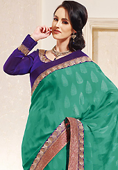 The evolution of style species collection spells pure femininity. This green faux crepe jacquard saree is nicely designed with embroidered patch work is done with zari work. This saree gives you a modern and different look in fabulous style. Contrasting purple blouse is available. Slight color variations are possible due to differing screen and photograph resolution.