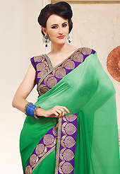 Try out this year top trend, glowing, bold and natural collection. This shaded green faux chiffon saree is nicely designed with embroidered patch work is done with zari, stone and lace work. This saree gives you a modern and different look in fabulous style. Contrasting purple blouse is available. Slight color variations are possible due to differing screen and photograph resolution.