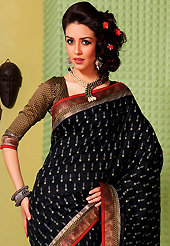 Exquisite combination of color, fabric can be seen here. This black art silk saree is nicely designed with floral print, self weaving zari, lace and patch bordered work. Beautiful embroidery work on saree make attractive to impress all. This saree gives you a modern and different look in fabulous style. Matching blouse is available. Slight color variations are possible due to differing screen and photograph resolution.