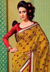 An occasion wear perfect is ready to rock you. This mustard art silk saree is nicely designed with floral print, self weaving zari, lace and patch bordered work. Beautiful embroidery work on saree make attractive to impress all. This saree gives you a modern and different look in fabulous style. Contrasting red blouse is available. Slight color variations are possible due to differing screen and photograph resolution.