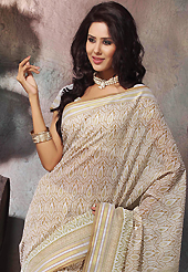 Make a trendy look with this classic printed saree. This beautiful off white and light brown cotton saree is nicely designed with abstract print and self weaving zari work. Beautiful print work on saree make attractive to impress all. It will enhance your personality and gives you a singular look. Matching blouse is available with this saree. Slight color variations are due to differing screen and photography resolution.