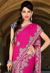 Look stunning rich with dark shades and floral patterns. This dark pink and deep purple satin chiffon and velvet lehenga style saree have beautiful embroidery patch work which is embellished with sequins, stone, cutdana and cutbeads work. Fabulous designed embroidery gives you an ethnic look and increasing your beauty. Matching blouse is available. Slight Color variations are possible due to differing screen and photograph resolutions.