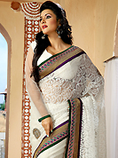 An endearing splash oh colors look gorgeous tridimensional charm. This off white net saree is nicely designed with embroidered patch work is done with resham, zari and stone work. Beautiful embroidery work on saree make attractive to impress all. This saree gives you a modern and different look in fabulous style. Matching blouse is available. Slight color variations are possible due to differing screen and photograph resolution.