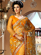 Keep the interest with this designer embroidery saree. This dark orange net saree is nicely designed with embroidery and velvet patch work is done with resham, zari, sequins, stone and lace work. Beautiful embroidery work on saree make attractive to impress all. This saree gives you a modern and different look in fabulous style. Matching blouse is available. Slight color variations are possible due to differing screen and photograph resolution.